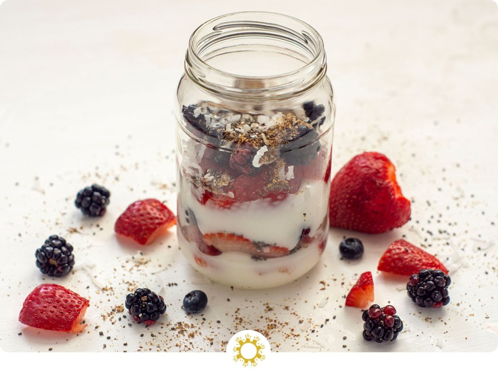Yogurt parfait in a mason jar on a white background with extra ingredients around it (with logo overlay)