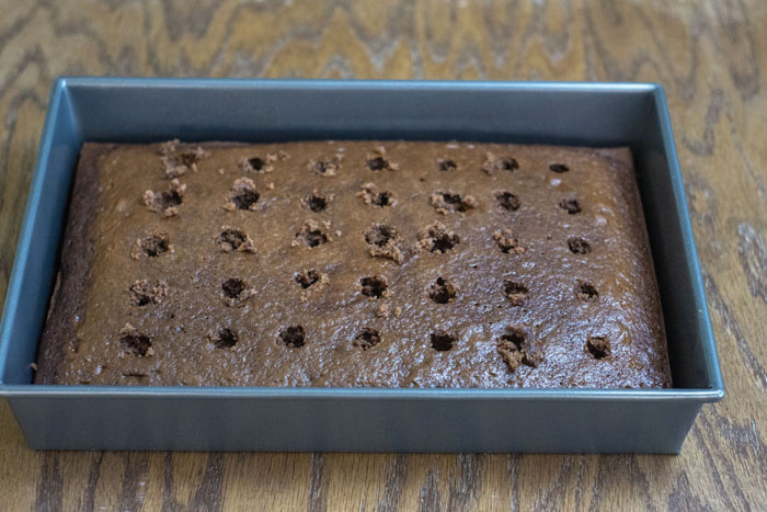 Chocolate cake with holes poked in it in a metal baking pan on a wooden surface