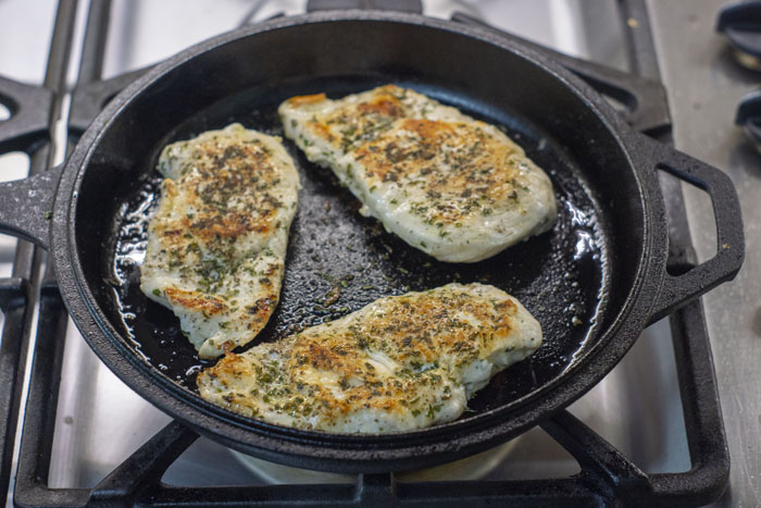 Three seasoned chicken breasts cooking in oil in a cast iron pan on a gas stovetop