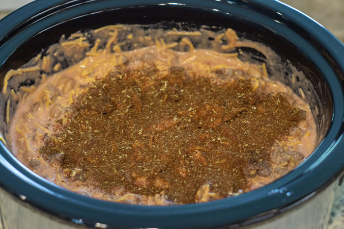 Chili nacho dip in the slow cooker with seasoning on top ready to be mixed in