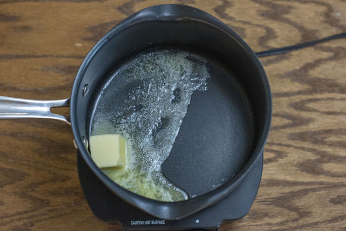 Butter melting in a small saucepan on a portable cooktop on a wooden surface