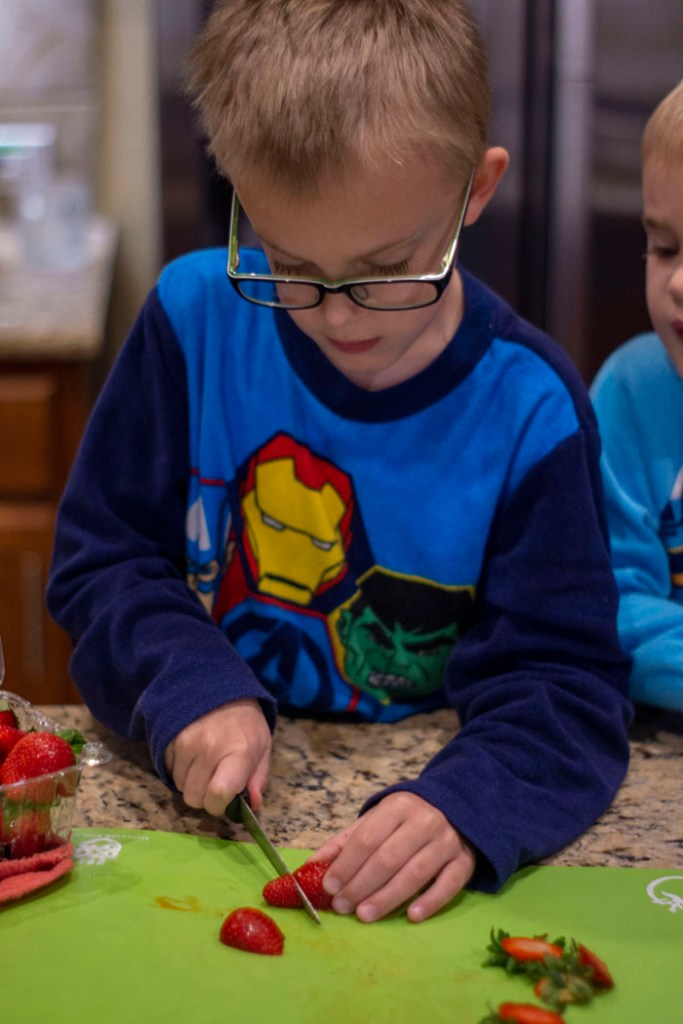 Young boy slicing strawberries on a green cutting board