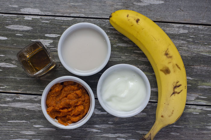 """""""mise en place"""" for a pumpkin pie smoothie: 3 white bowls with pumpkin puree, almond milk, and greek yogurt, a banana, and maple syrup all on a wooden surface"""