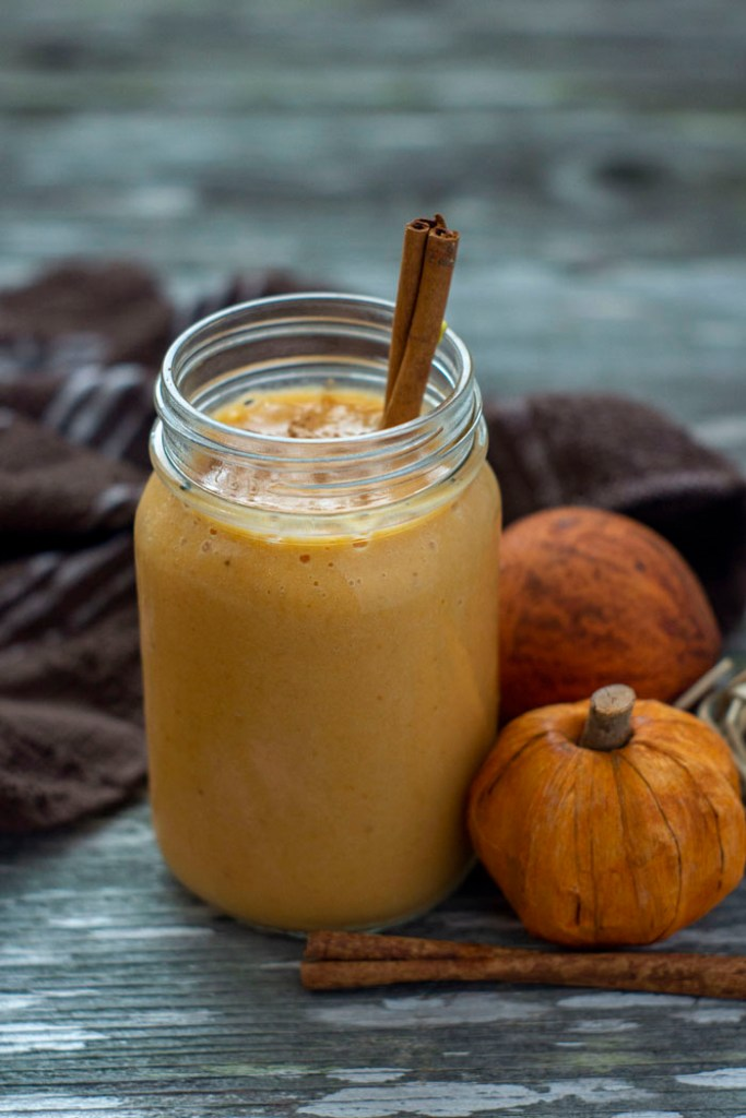 Pumpkin pie smoothie in a large mason jar with a stick of cinnamon sticking out next to fall decorations and a brown towel on a wooden surface (vertical)