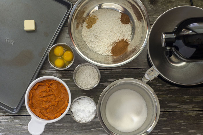 """""""mise en place"""" for pumpkin roll: stainless steel bowls with flour mixture, sugar, powdered sugar, dry milk, eggs, and pumpkin puree, a stand mixer, and a metal sheet pan with a pat of butter on it all on a wooden surface"""
