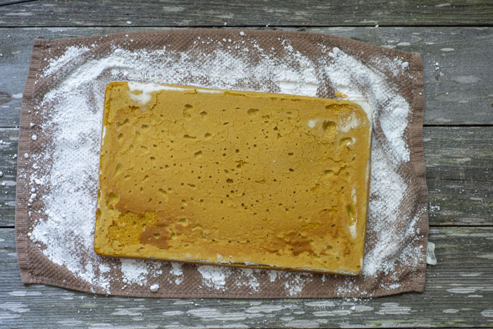Overhead view of baked pumpkin cake on a brown dish towel that has been sprinkled with powdered sugar all on a wooden surface