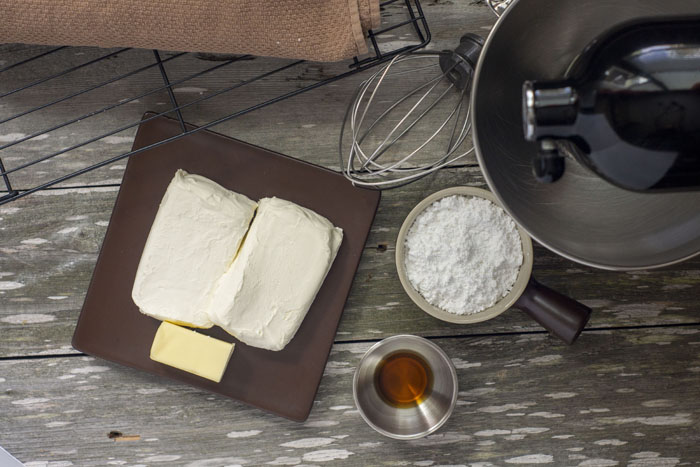 """""""mise en place"""" of the frosting for pumpkin roll: a square brown plate with 2 blocks of cream cheese and a piece of butter next to a bowl with powdered sugar and another bowl with vanilla extract. A stand mixer and whisk attachment are to the side and the rolled cake is on a cooling rack in the background."""