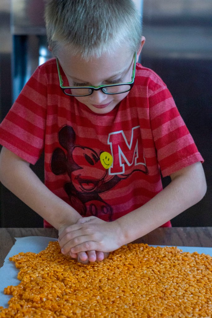 Young boy using a pumpkin-shaped cookie cutter to cut rice krispies