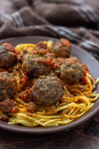 Spaghetti and Homemade Meatballs on a round brown plate next to a brown towel on a wooden surface (vertical)