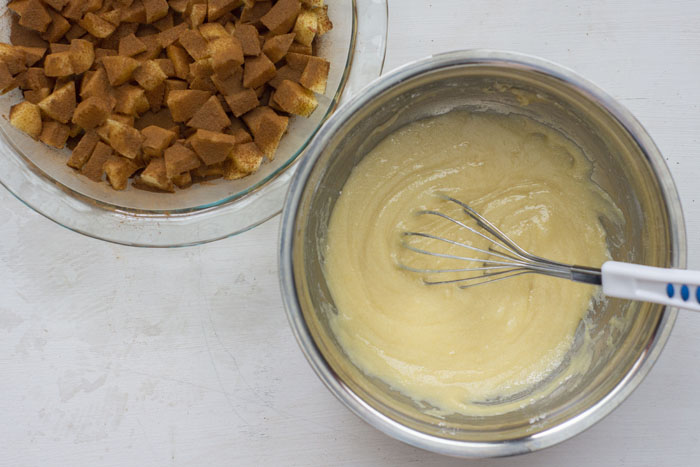 Large stainless steel bowl with batter and a wire whisk next to a glass pie pan with chunks of apple covered in cinnamon all on a grey and white surface