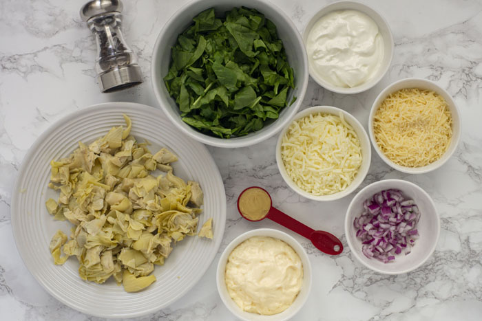 White bowls and plates with baked spinach artichoke dip ingredients on a white and grey marble surface
