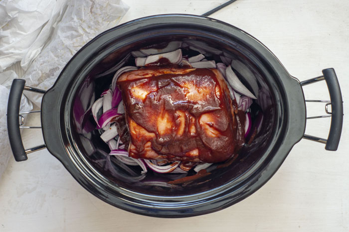 Slow cooker containing sliced red onions topped with a pork roast lathered with bbq sauce sitting next to potatoes wrapped in parchment paper on a white surface