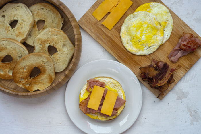 Bamboo bowl of toasted bagel slices next to a wooden cutting board with slices of cheese, cooked eggs, and cooked bacon and ham by a round white plate with a bagel topped with egg, ham, and cheese on a white and grey surface