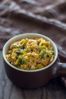 Cheesy Rice Casserole with Chicken and Broccoli in a brown serving dish with a brown and white towel behind all on a wooden surface (vertical)