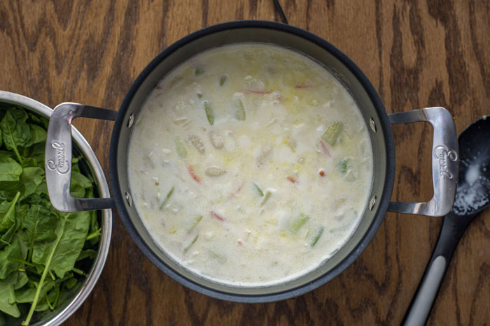 Large stockpot with vegetables and gnocchi visible in the cream soup next to a stainless steel bowl of spinach leaves and a stirring spoon all on a wooden surface