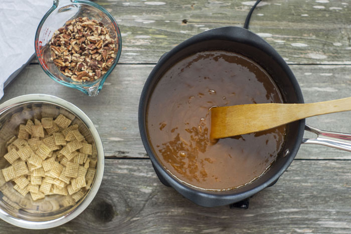 Saucepan with melted caramels and a wooden spoon inside sitting next to a stainless steel bowl of rice square cereal and a glass measuring cup of chopped pecans all on a wooden surface