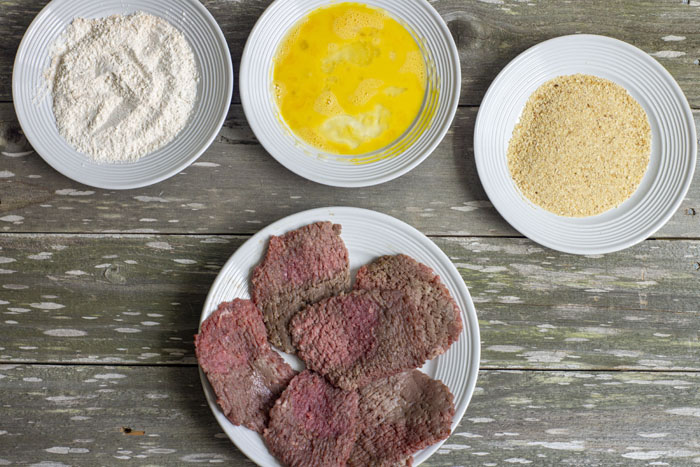Three round plates covered with flour on one, egg on another, and breadcrumbs on the third above another round plate with cube steaks all on a wooden surface