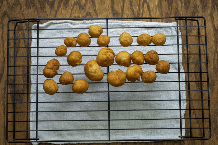 Fried doughnut holes on a wire cooling rack with a white towel underneath all on a wooden surface