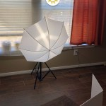 Behind the scenes of food on a white plate with a towel and fork on a small wooden board with a white foam board reflector behind it and an umbrella light in front (vertical with title overlay)