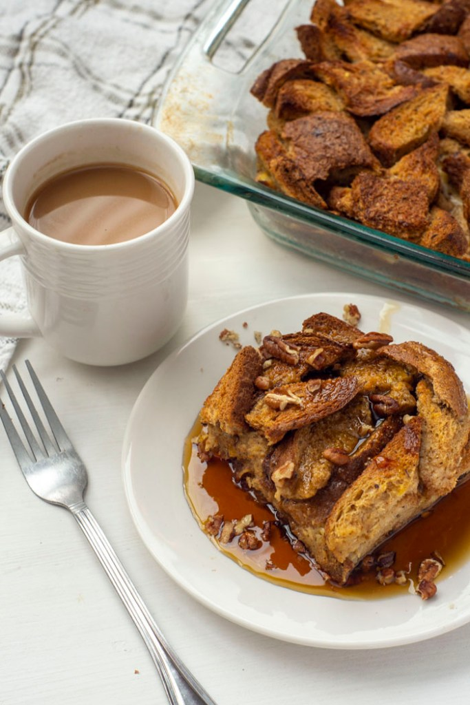 French Toast Casserole topped with chopped pecans and maple syrup on a round white plate next to a fork and a white cup of coffee with the dish of remaining casserole and a white towel in the background all on a white surface (vertical)