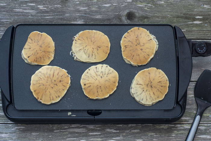 Six cooked small pancakes on a large flat skillet on a wooden surface