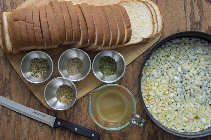 Loaf of sliced bread next to stainless steel bowls of dried herbs on a wooden cutting board next to a glass measuring cup of chicken broth and a bread knife beside a frying pan with cooked onions all on a wooden surface