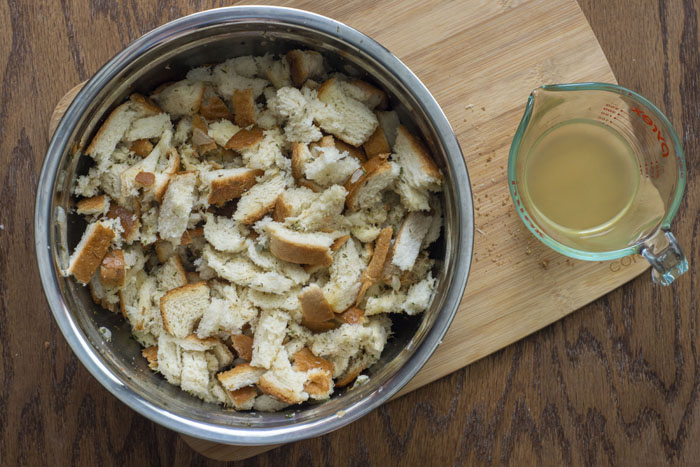 Large stainless steel bowl filled with chopped bread pieces covered with herbs and cooked onions next to a glass measuring cup of chicken broth on a wooden cutting board on a wooden surface