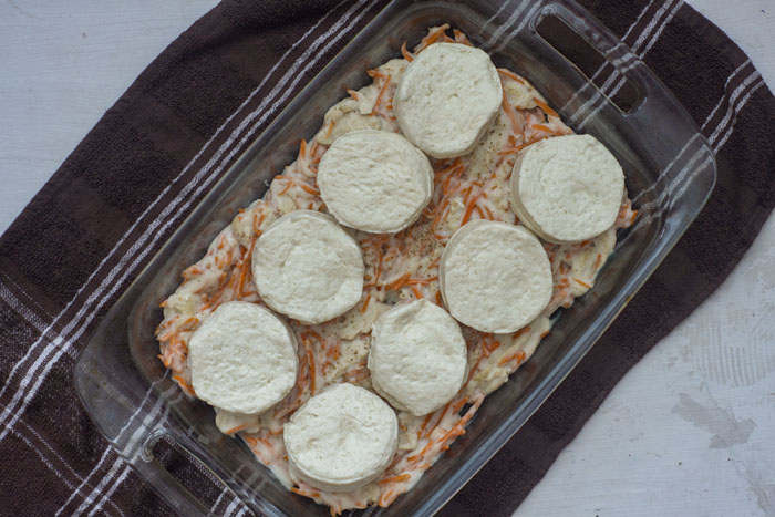 Glass baking dish filled with a mixture of gravy, shredded chicken, and shredded carrots on a brown towel on a white wooden surface topped with uncooked biscuits