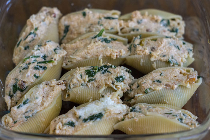 Stuffed shells in a glass baking dish on a wooden surface