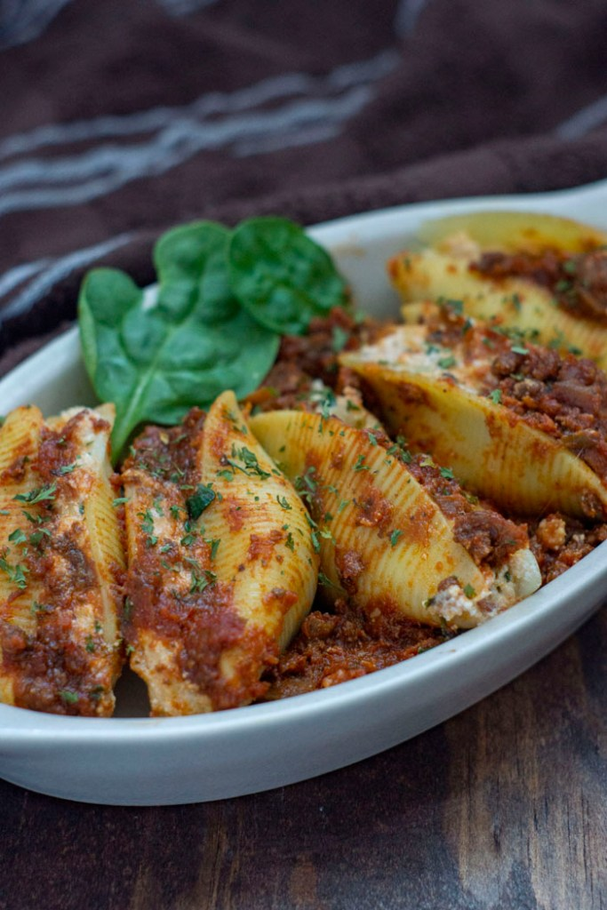 Cooked stuffed shells garnished with spinach in a white dish on a wooden surface (vertical)