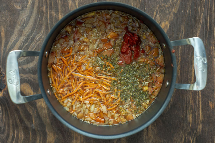 Large stockpot of broth with diced onions, shredded carrots, tomato paste, and seasonings on a wooden surface