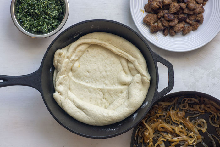 Large cast-iron skillet with pizza dough next to a stainless steel bowl of kale pesto, a white plate with cooked sausage, and another skillet with cooked onions all on a white surface