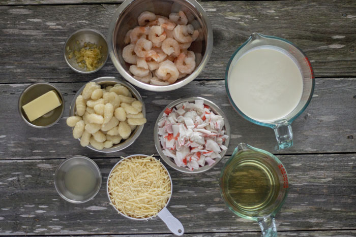 Ingredients for seafood gnocchi soup in place: stainless steel bowls with shrimp, chopped crab, potato gnocchi, minced garlic, butter, and lemon juice next to glass measuring cups of cream and broth and a measuring cup of shredded parmesan cheese all on a wooden surface