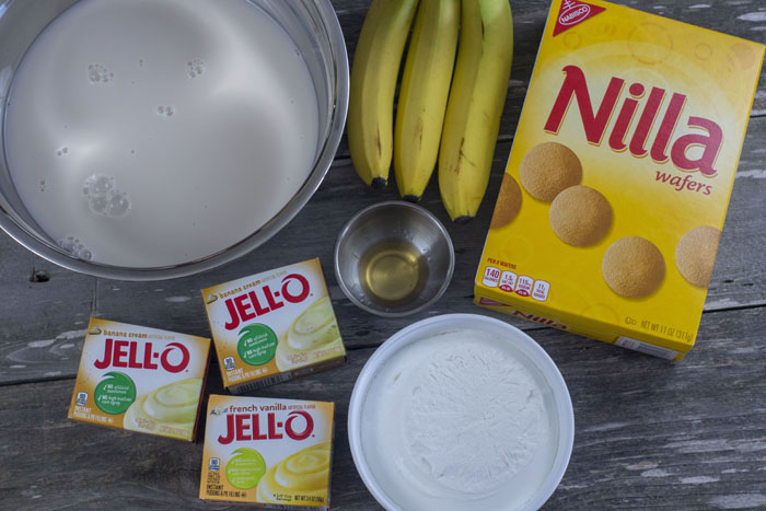 Ingredients for banana pudding: stainless steel bowl of milk, bananas, a box of nilla wafters, 3 packs of jello, vanilla extract, and whipped topping all on a wooden surface