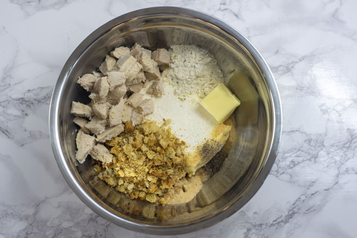 Stainless steel bowl with all chicken biscuit ingredients ready to be mixed: chicken, ranch powder, butter, cream cheese, crushed croutons, and seasonings