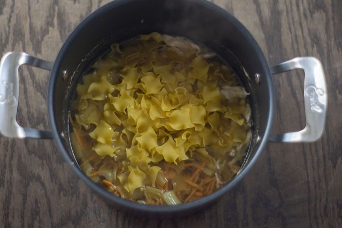 Large stockpot with warm soup topped with uncooked egg noodles over a wooden surface