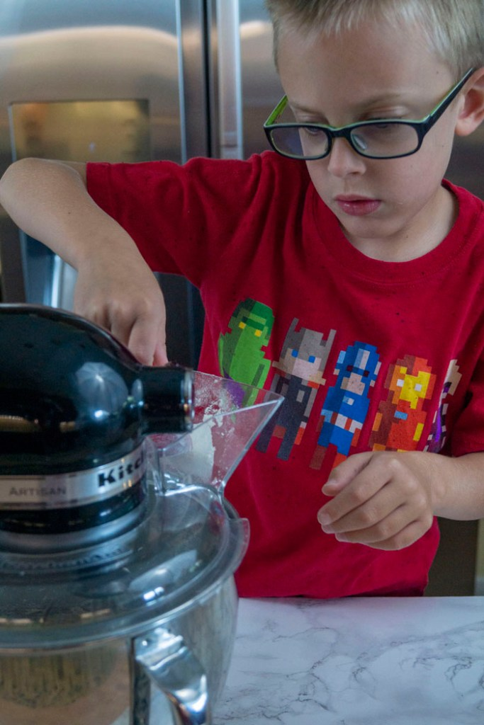 Young boy pouring dry ingredients into a stand mixer on a white and grey marble surface