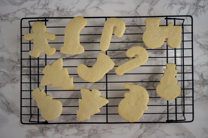 Baked Christmas sugar cookies on a wire cooling rack over a white and grey marble surface
