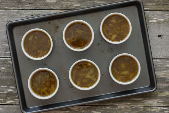 6 small white ramekins filled with onion soup sitting on a metal baking pan on a wooden surface