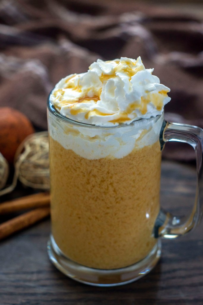 Glass mug of spiked hot apple cider topped with whipped cream and caramel sauce with fall decorations behind all on a wooden surface (vertical)