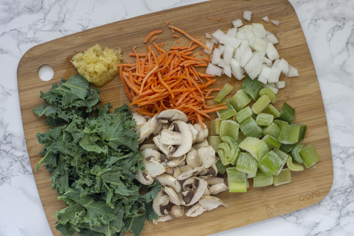 Bamboo cutting board with shredded kale, minced garlic, shredded carrots, diced onion, diced celery, and sliced mushrooms on a white and grey marble surface