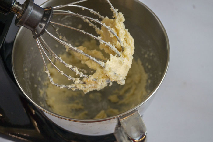 Whisk attachment lifting whisked butter and sugar from a stand mixer on a white surface