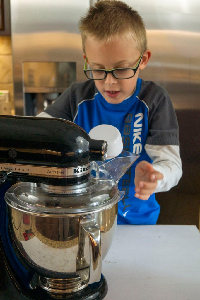 Young boy pouring ingredients into a stand mixer