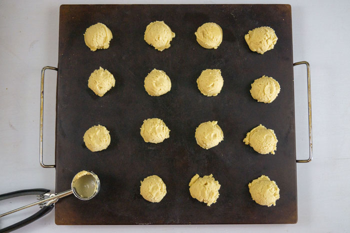 Balls of cookie dough on a baking stone with a cookie scoop on a white surface
