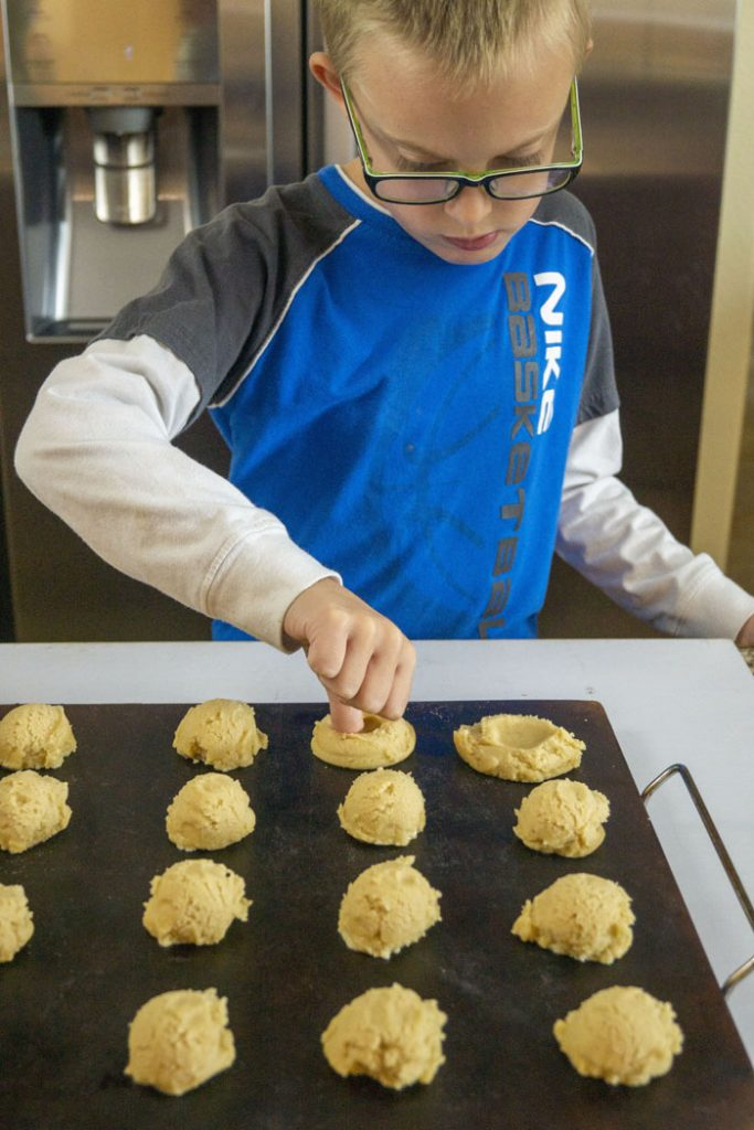 Young boy pressing thumbprints into balls of cookie dough on a baking stone on a white surface