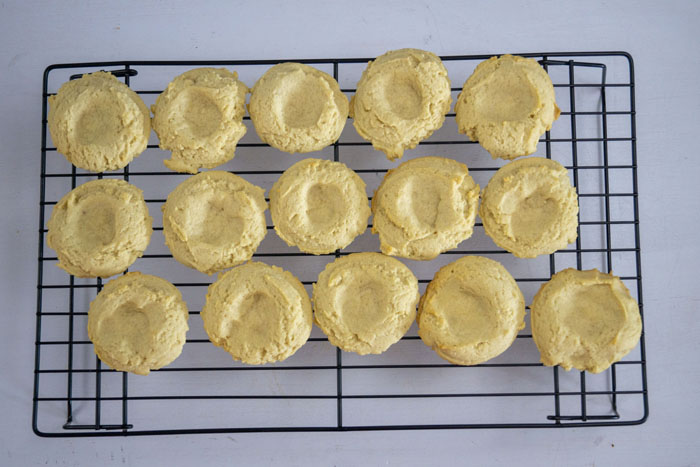 Baked thumbprint cookies on a wire cooling rack on a white surface