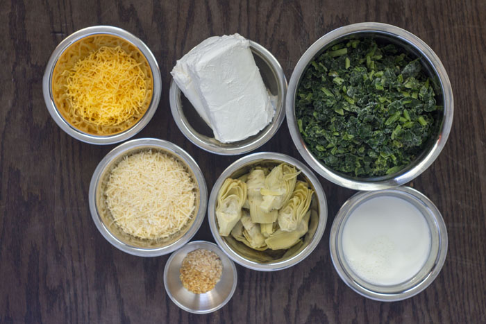 Ingredients ready for spinach artichoke dip: stainless steel bowls with shredded cheddar cheese, cream cheese, frozen spinach, shredded parmesan cheese, chopped artichoke hearts, milk, and minced garlic all on a wooden surface
