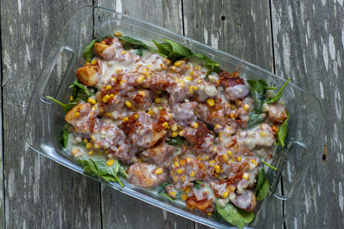 Cooked potatoes, tomato sauce, diced onions, and corn kernels on top of a bed of spinach leaves covered with a milk mixture in a glass baking dish on a wooden surface