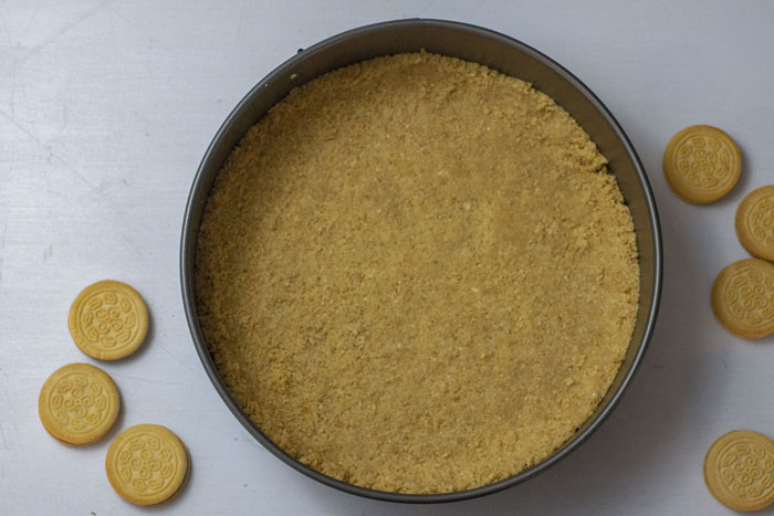 Springform pan with cookie crumble crust pressed into the pan with whole cookies around it on a white surface