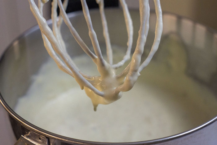 Whisk attachment of a stand mixer lifted from the mixing bowl with bits of batter dripping off
